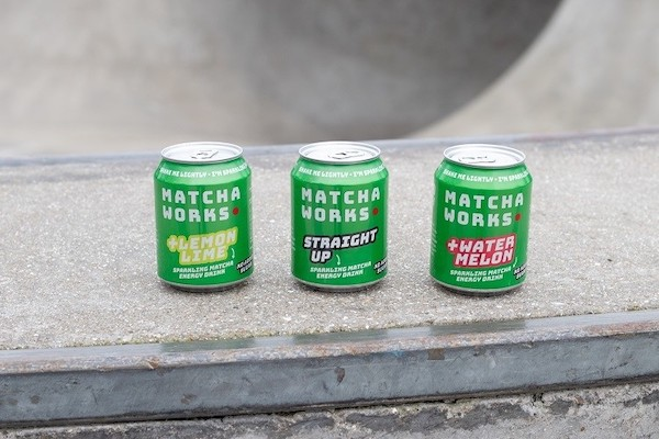 three small green 'Matcha Works' cans on a concrete wall