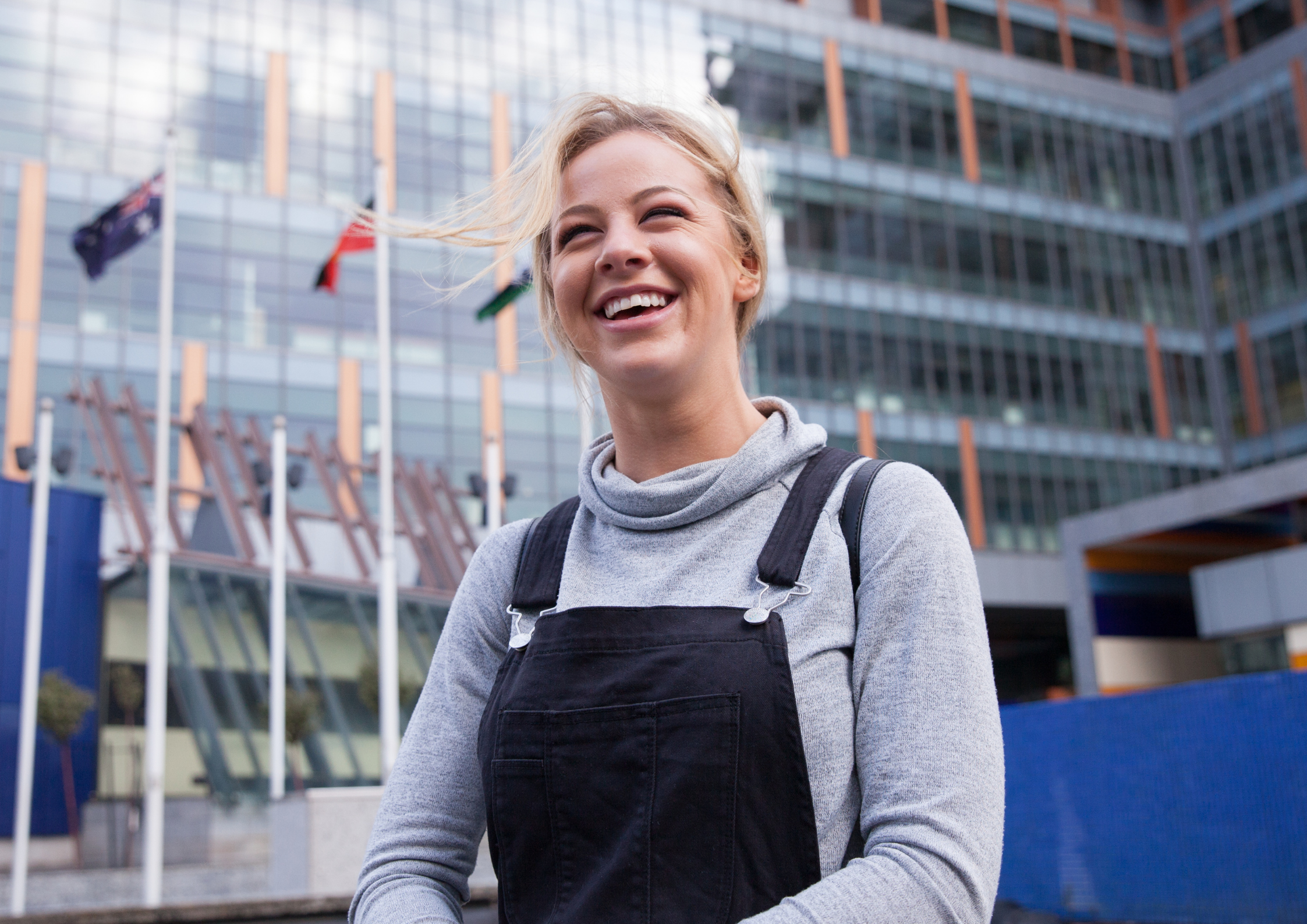 young woman smiling in front of a shiny office building
