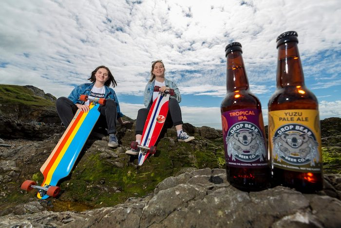 Two women with surfboards on a rock with two bottles of beer in the foreground
