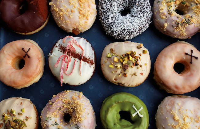 12 doughnuts with various toppings, photo taken from above