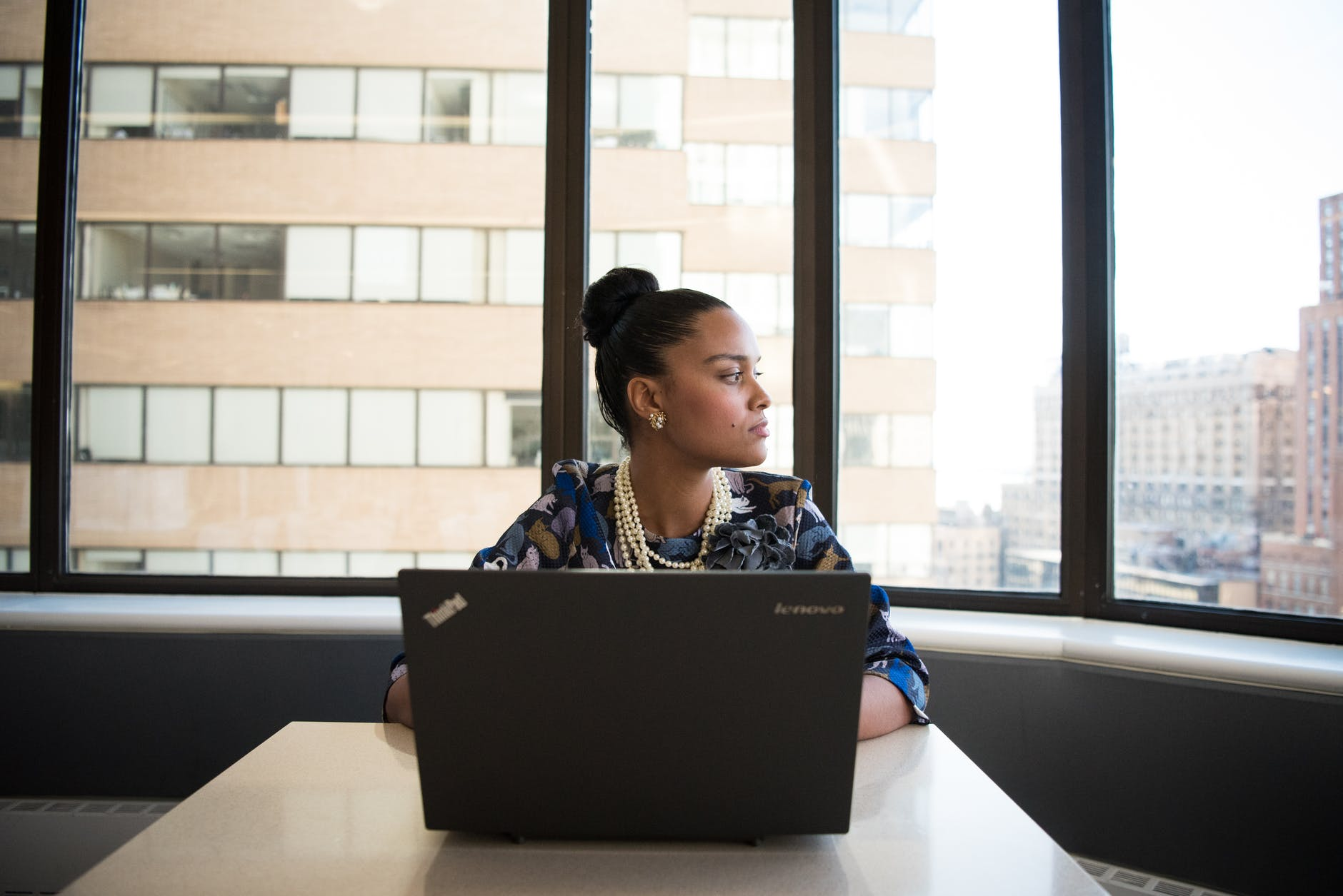 Woman on laptop looking outside office window