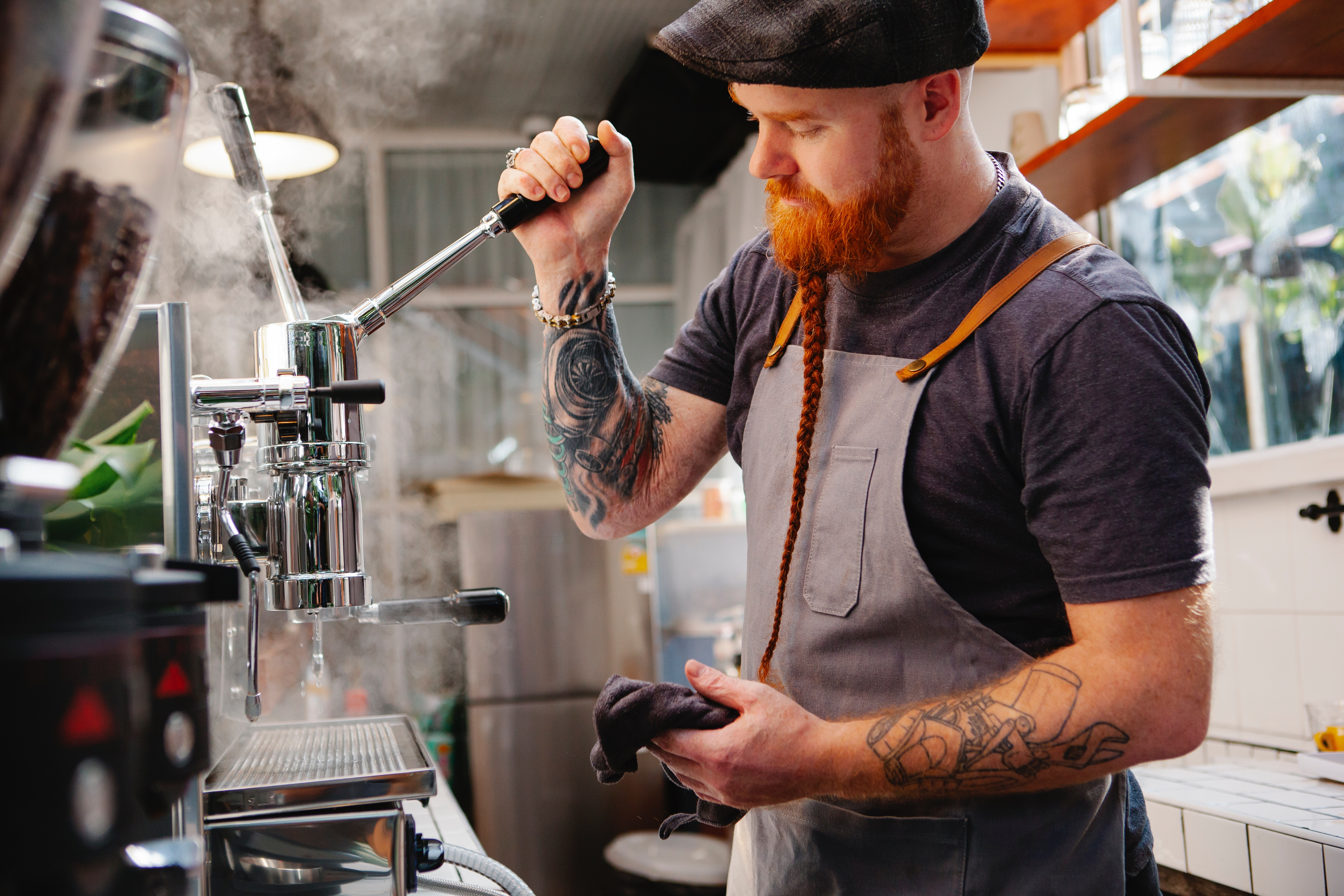 Male barista with ginger hair and long plaited beard making a coffee