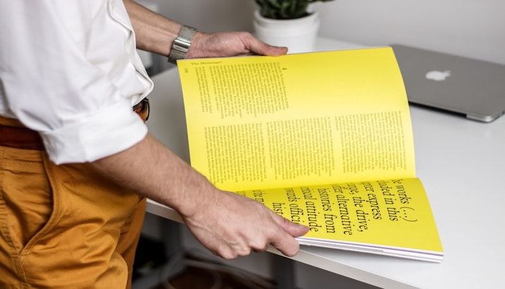 Man reading a yellow magazine